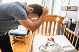 Väter-Zweifel: Vater steht verzweifelt am Bett seines Babys