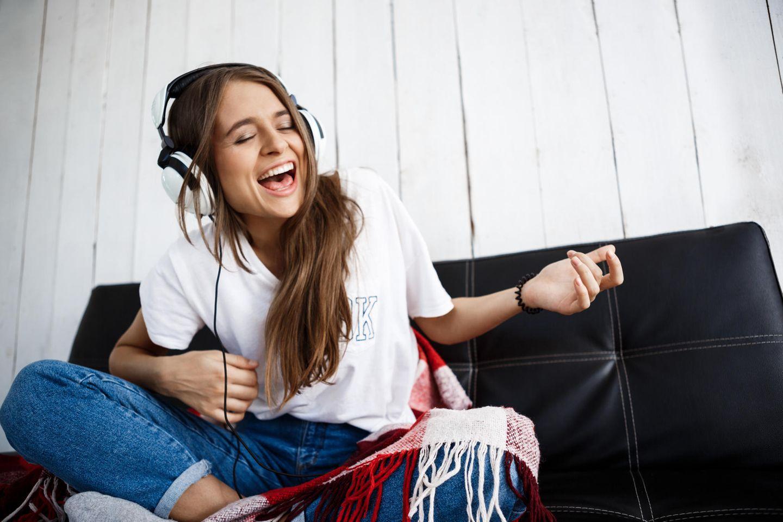 Eine Frau spielt Luftgitarre mit Kopfhörern