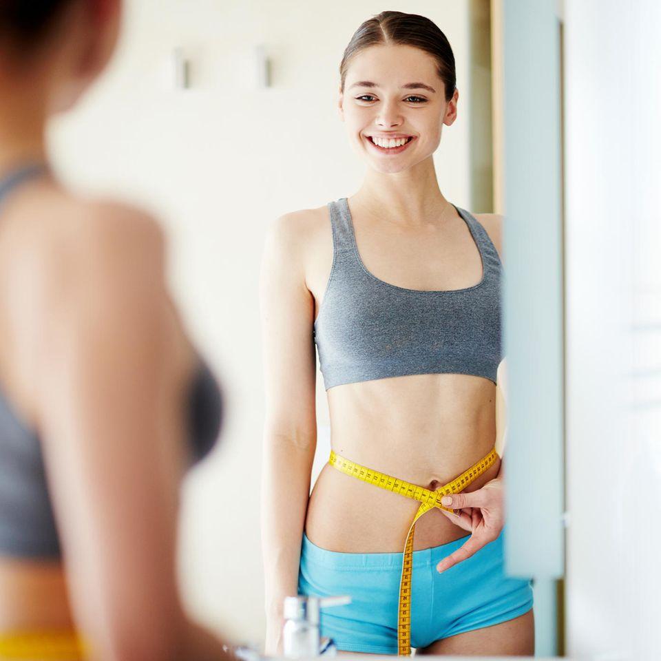 Frau steht vor dem Spiegel und hält sich ein Maßband an die Hüfte