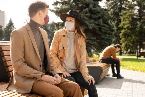 Ein Paar mit Gesichtsmasken auf einer Bank im Park