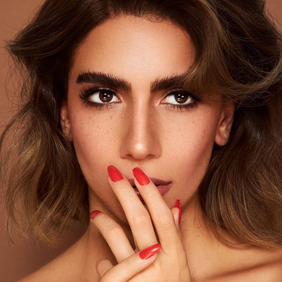 Geschminkte Frau mit lackierten Nägeln hält die Finger an den Mund