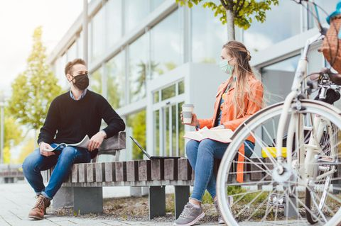 Ein Mann und eine Frau sitzen mit Maske auf einer Bank