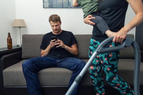 Hausfrau oder -mann: Mann sitzt auf Sofa während Frau aufsaugt