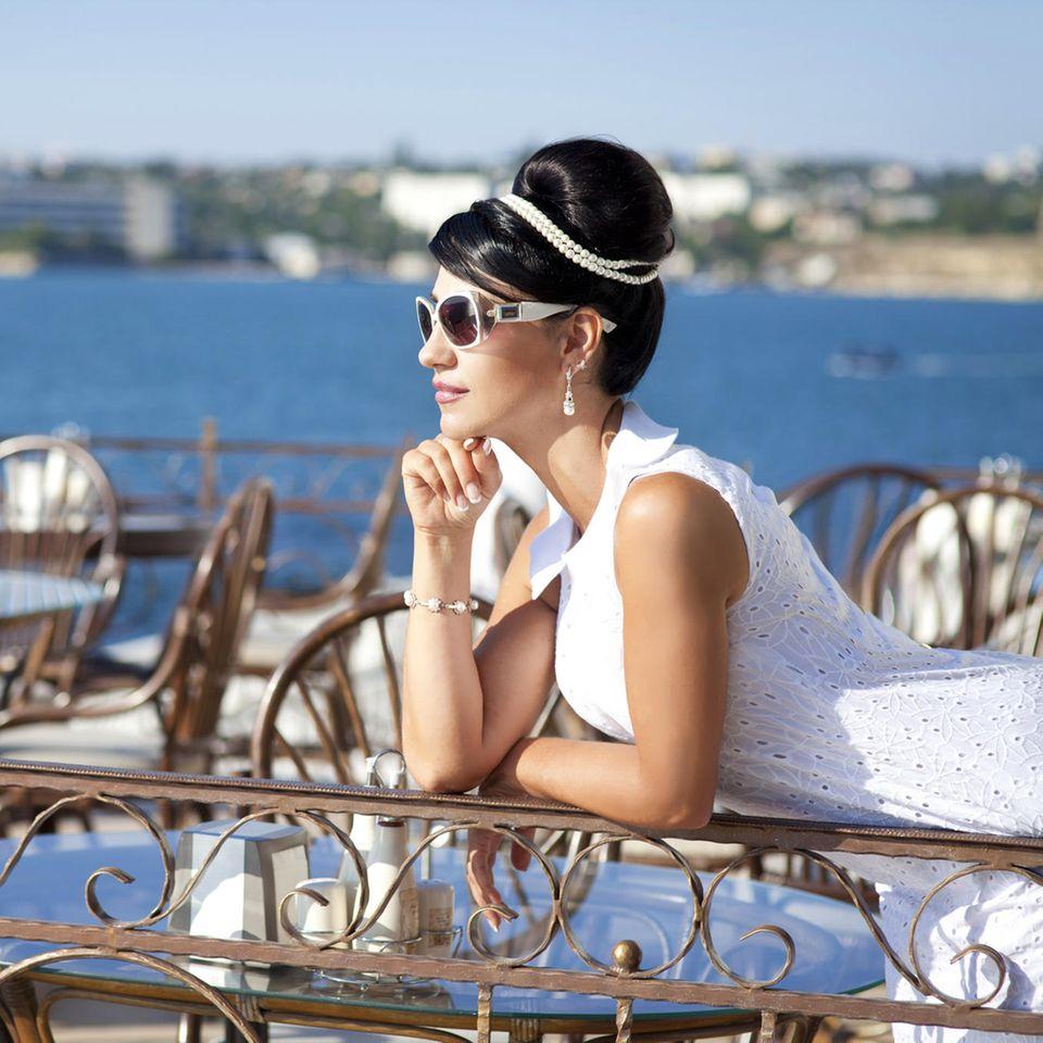 Macht Geld glücklich? Eine reiche Frau in einem Café am Meer