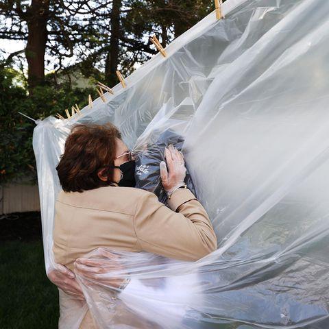 Bewegende Momente 2020: Frau umarmt Tochter durch Plastikfolie