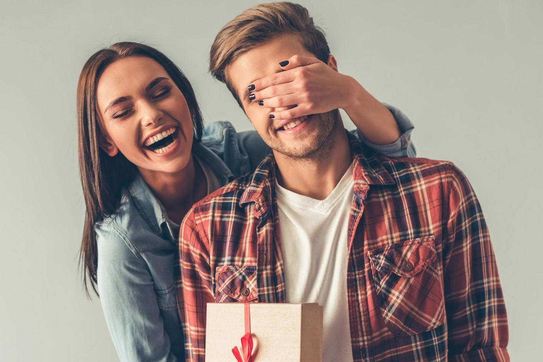 Geschenk Bruder: junge Frau und junger Mann, Frau hat ein Geschenk für Mann, Mann hat Hand der Frau vor den Augen