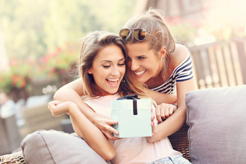 Verlobungsgeschenk: Junge Frauen überreichen Geschenk, Geschenk geben, Freunde Geschenk