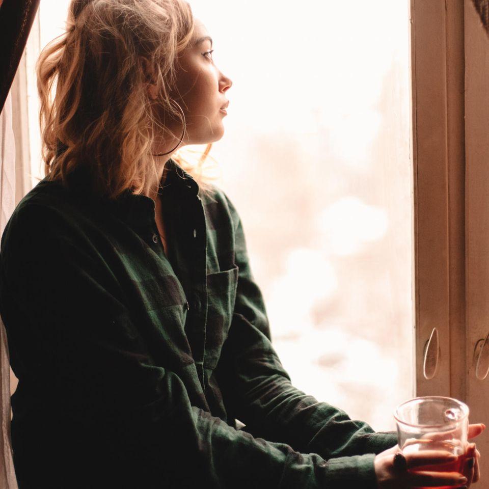 Eine nachdenkliche, junge Frau sitzt am Fenster und schaut raus