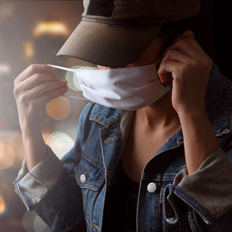 Corona aktuell: Eine Frau mit Kappe setzt ihre Maske auf