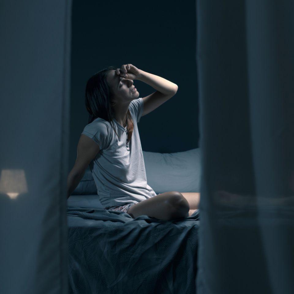 Mit offenem Fenster schlafen: Müde Frau im Dunklen