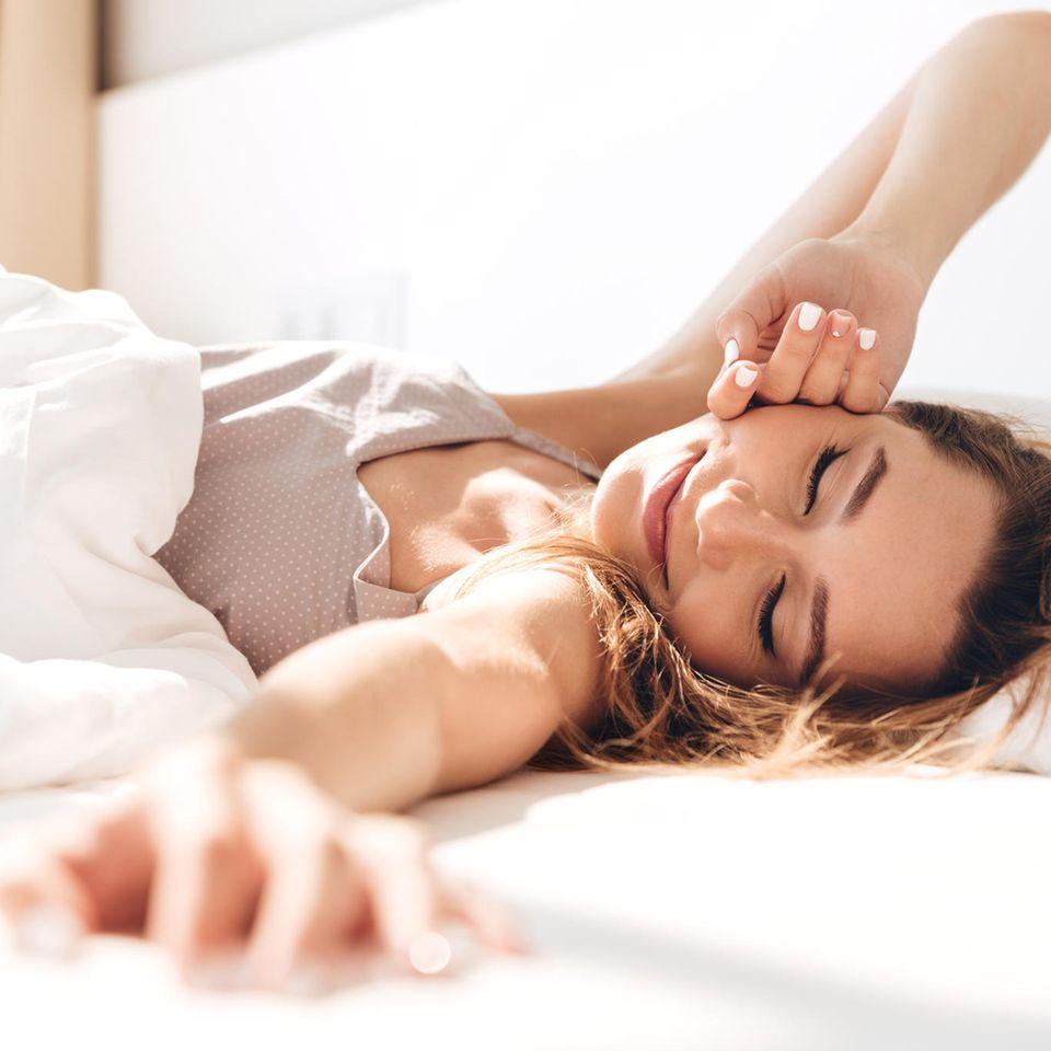 Glückliche Frau liegt im Bett und streckt sich