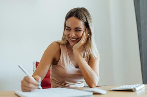 Motorischer Lerntyp: Frau sitzt am Schreibtisch und macht Notizen.
