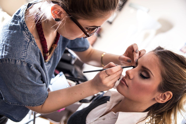 Maskenbildner: Maskenbildnerin schminkt Frau