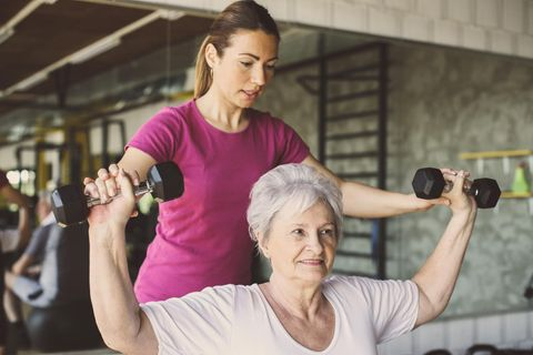 Sport- und Fitnesskaufmann: Sport- und Fitnesskauffrau trainiert mit älterer Dame