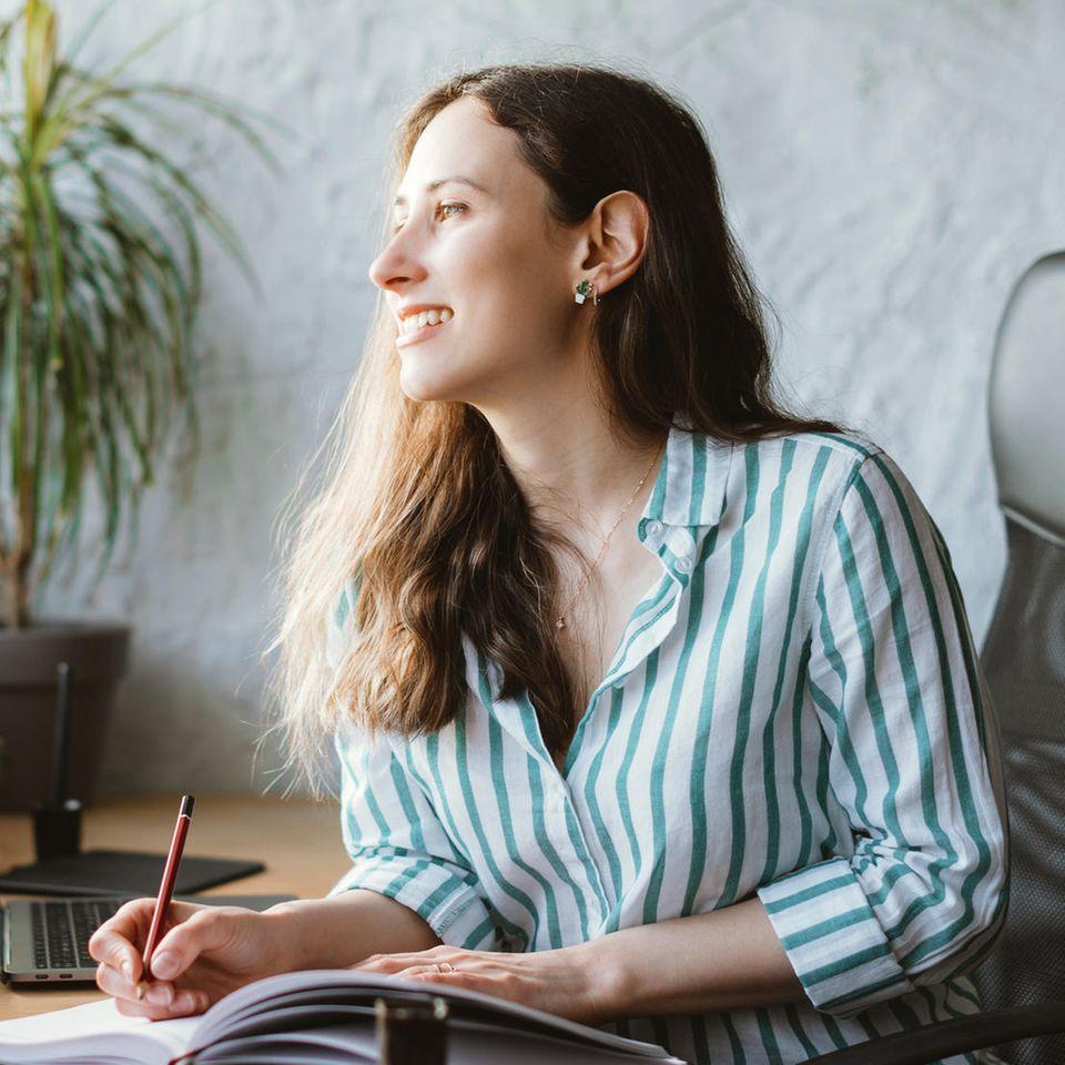 Entscheidungen treffen: Frau am Schreibtisch mit Notizbuch