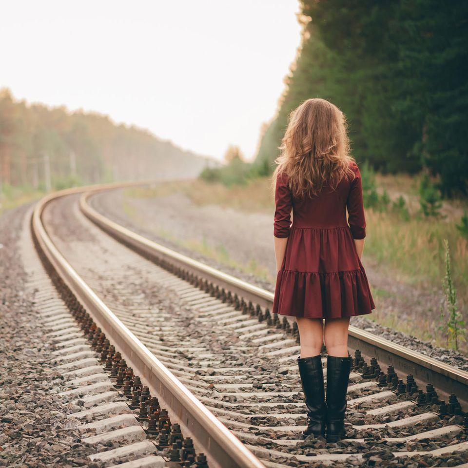 Verhaltensökonomie: Eine Frau steht auf Bahngleisen und schaut in die Weite