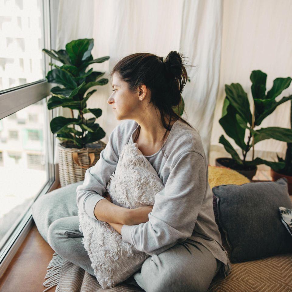 Depression durch Corona: Frau schaut nachdenklich aus dem Fenster