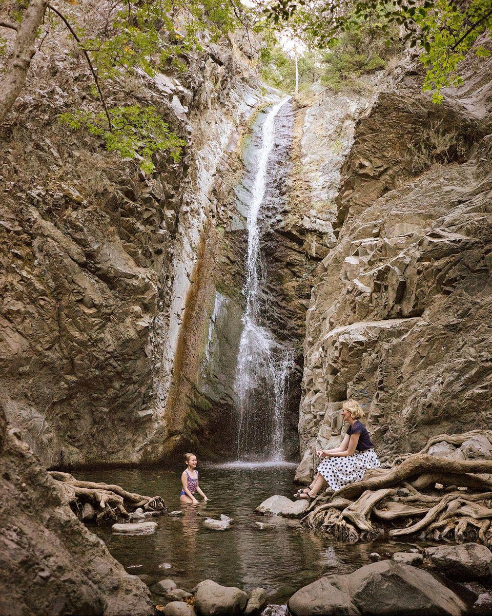 Zypern: Mädchen steht im Wasser am Wasserfall