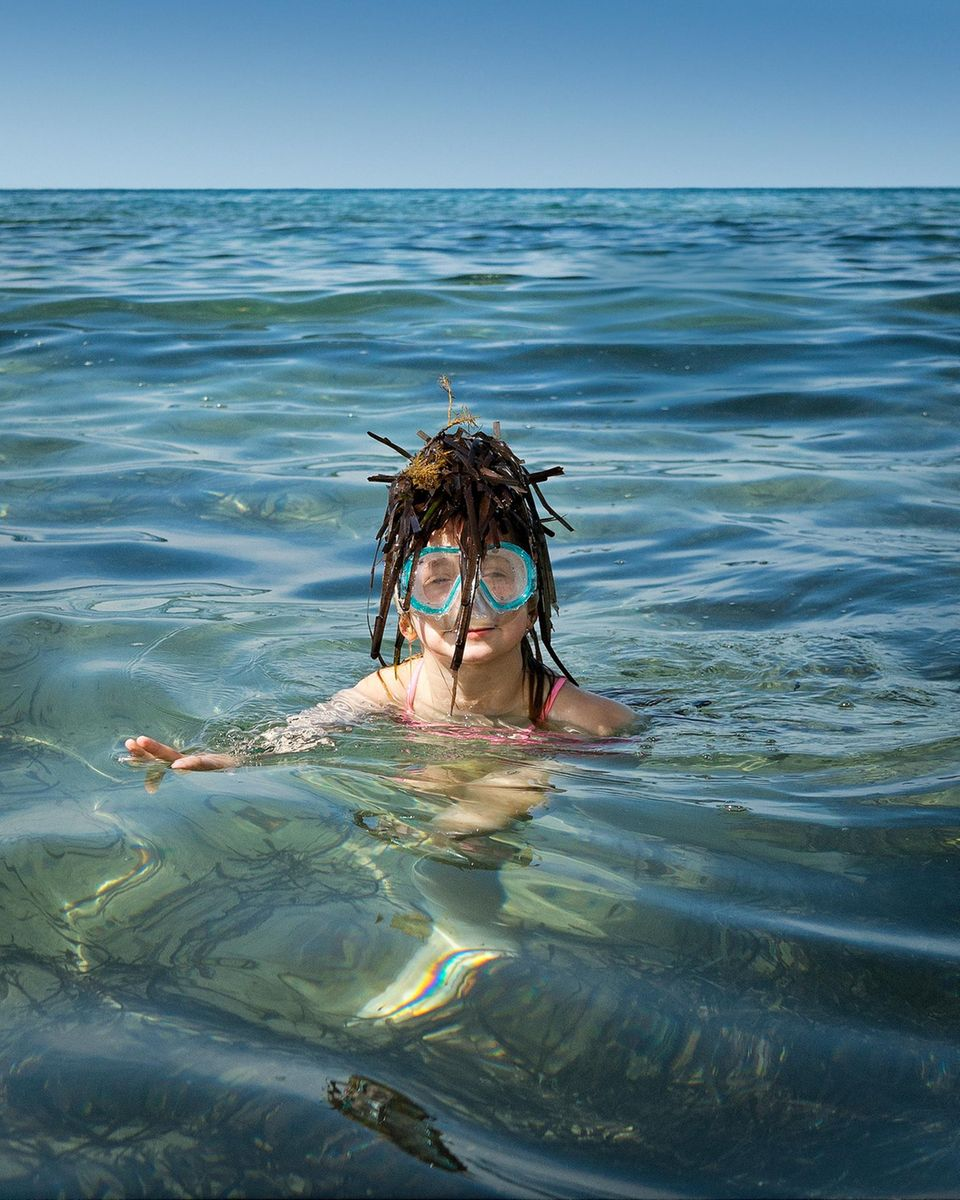 Zypern: Mädchen im Wasser mit Algen auf dem Kopf