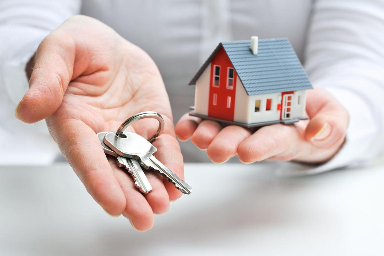 Immobillienmakler miit Schlüssel und Haus