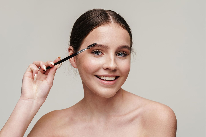 Junge Frau stylt sich die Augenbrauen
