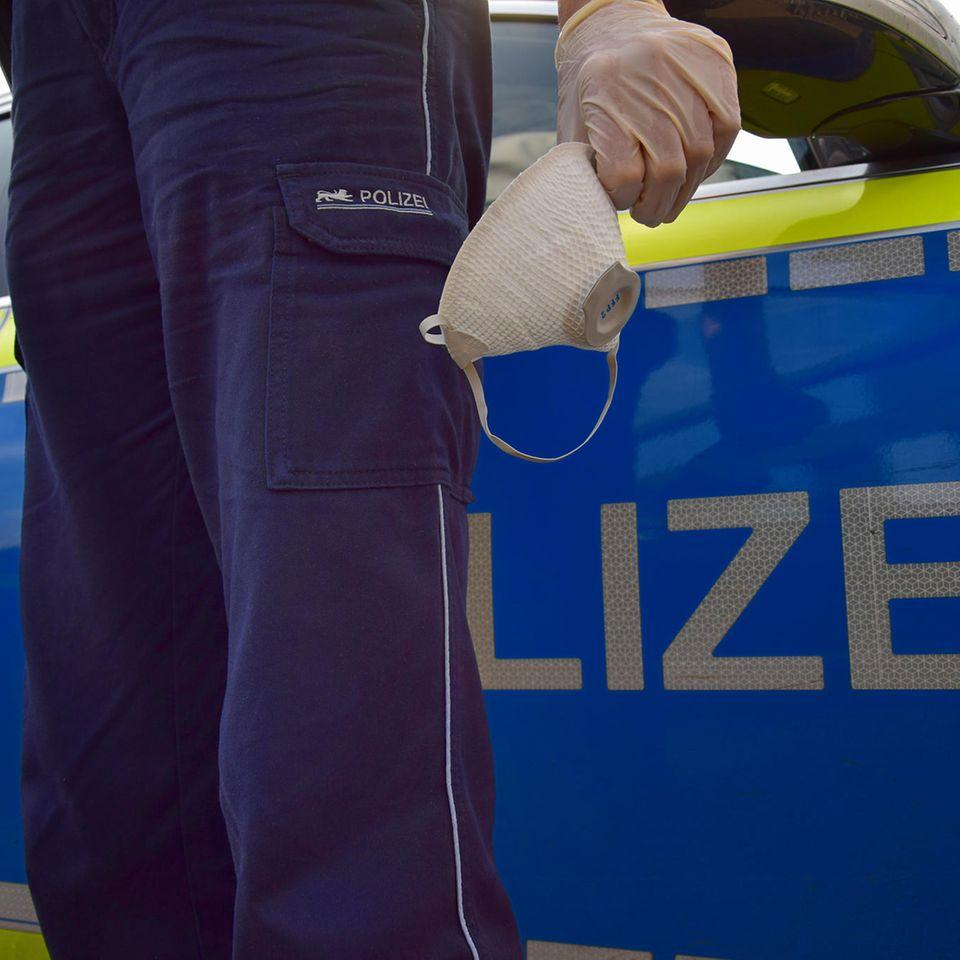 Corona aktuell: Polizei mit Maske in der Hand