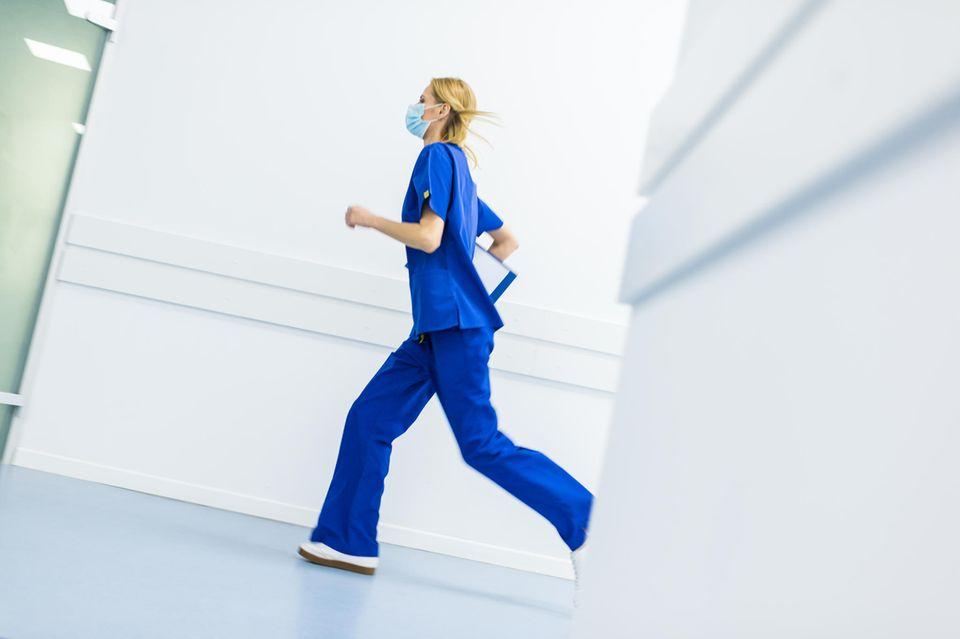 Pflegenotstand: Laufende Pflegerin mit Maske
