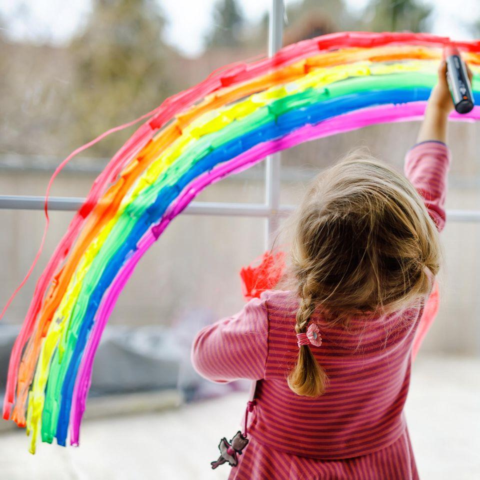 Kreidestifte Fenster: kleines Mädchen malt auf Fenster, Fensterdeko, Kinderbeschäftigung