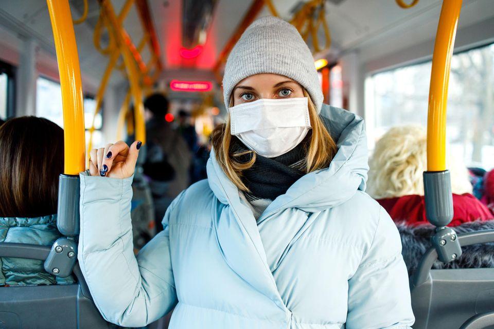 Corona aktuell: Frau im Bus mit Maske