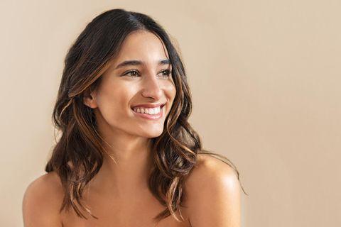 Schöne Frau mit langen Haaren lächelt in die Ferne