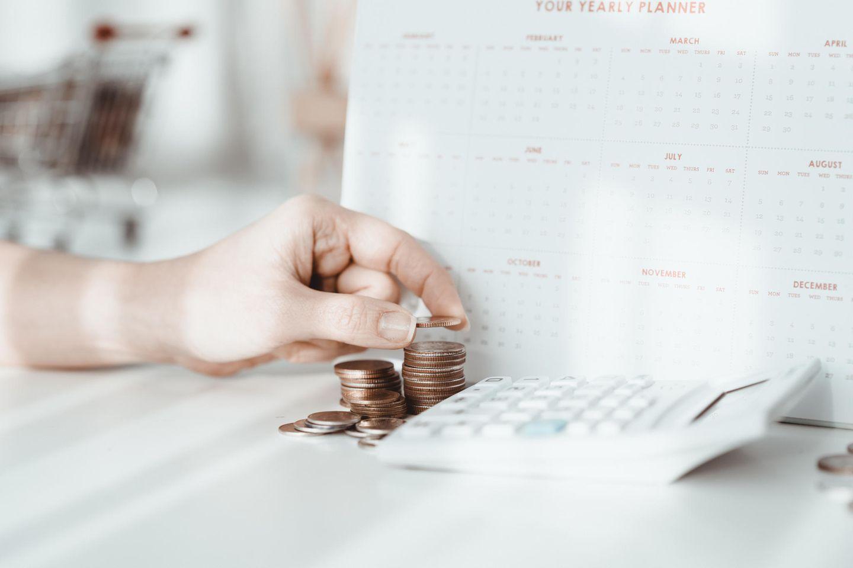 Geld anlegen: Frau stapelt Geld vor Taschenrechner