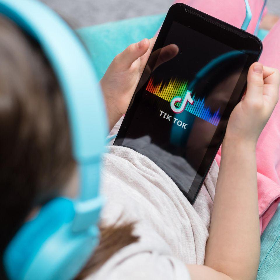 10-Jährige stirbt nach TikTok-Mutprobe: Mädchen hält Tablet, auf dem TikTok zu sehen ist