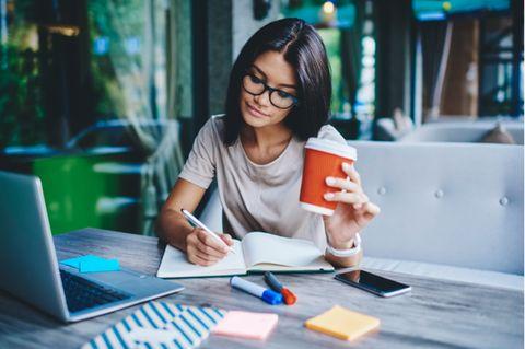 Schneller lernen: Frau sitzt am Schreibtisch und macht Notizen.