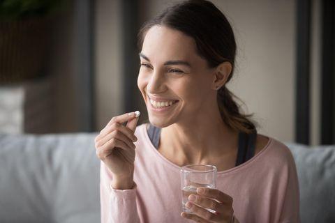 Frau nimmt Tablette mit einem Glas Wasser ein