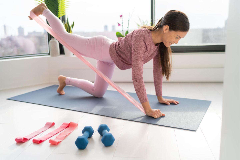 Frau in Sportklamotten führt Übung auf Sportmatte mit Fitnessband durch