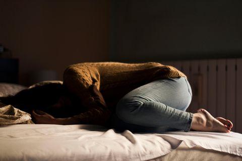 Frau liegt verzweifelt auf Bett