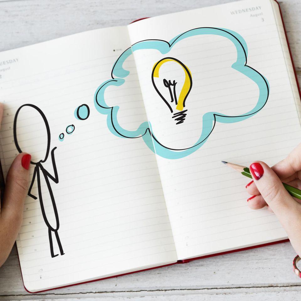 Corona aktuell: Eine Frau zeichnet in ein Ideentagebuch
