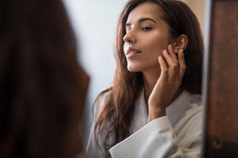 Schöne Frau betrachtet ebenmäßige Haut im Spiegel
