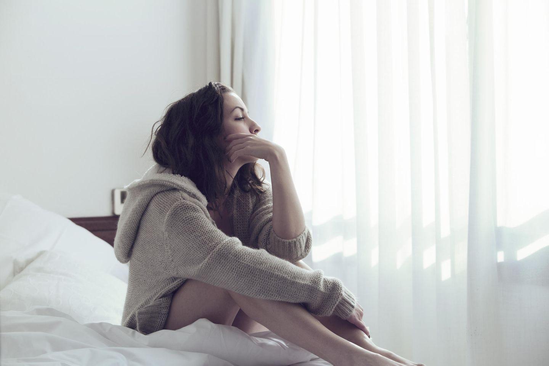 FOBO: Eine Frau sitzt grübelnd im Bett