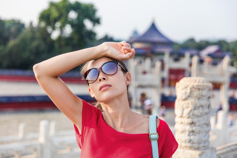 Frau schwitzt im Urlaub