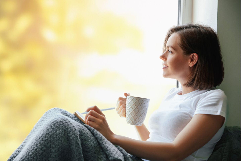 Selbstverantwortung: Frau sitzt am Fenster, trinkt Tee und schreibt in einem Notizbuch.