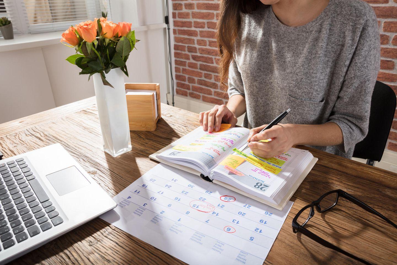 Selbstorganisation: Frau schreibt Notizen in einen Kalender.