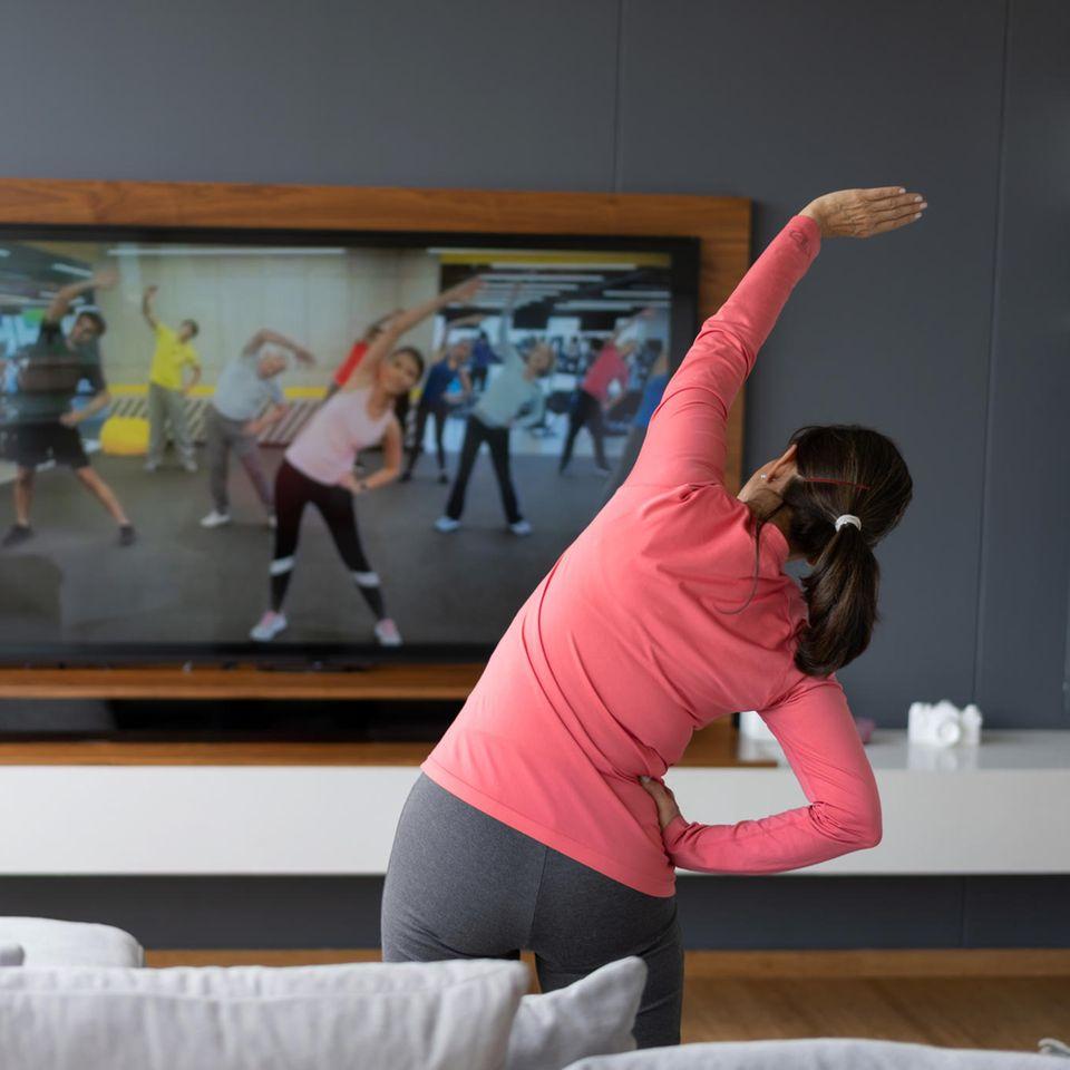Home-Workouts machen keinen Spaß: Frau macht Aerobic vor dem Fernseher