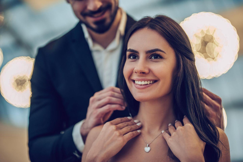 Valentinstagsgeschenke für die Freundin: Frau bekommt Kette von Mann, Mann legt Frau Kette um, Herzkette, Mann, Frau