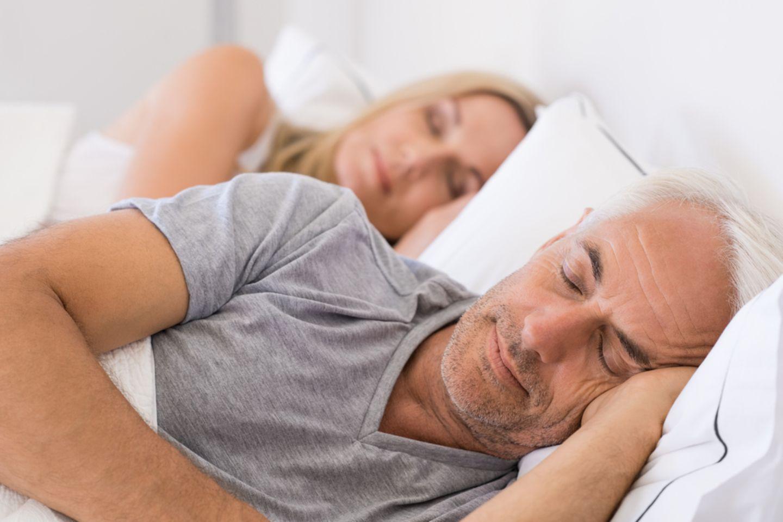 Schlafstörungen im Alter: Älterer Mann und ältere Frau schlafen