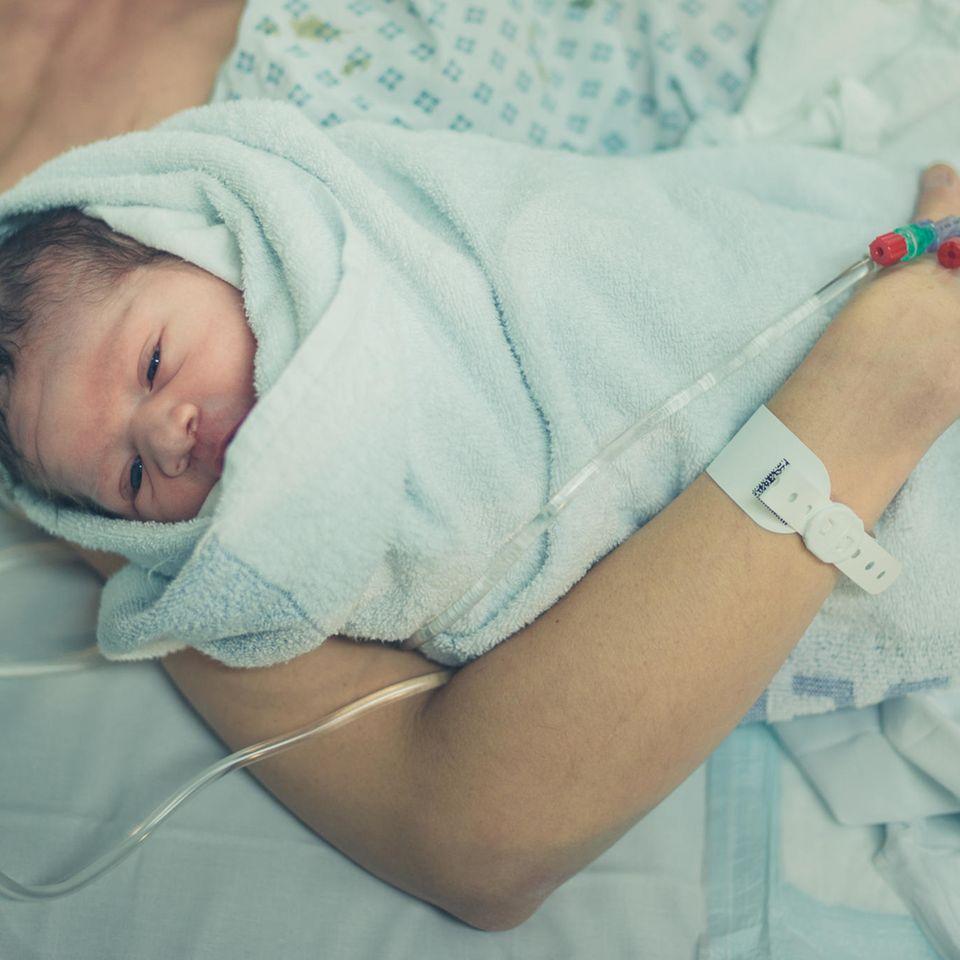 Corona aktuell: Eine Frau im Krankenhaus mit Baby im Arm