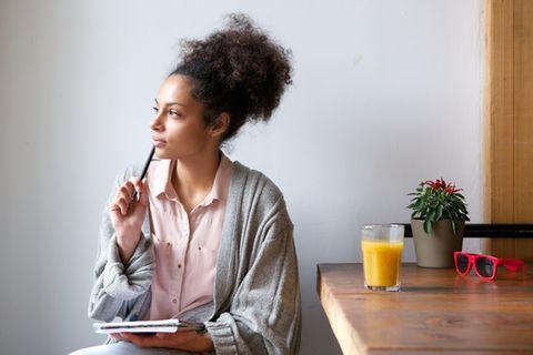 Kopfstandmethode: Frau sitzt am Schreibtisch und denkt nach.