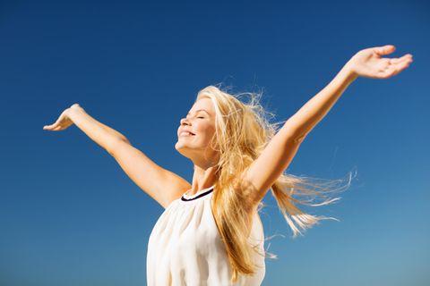 Selbstbewusstsein stärken: Selbstbewusste Frau hebt beide Arme in die Höhe
