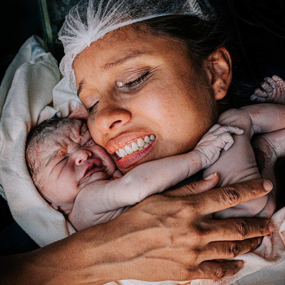 Geburtsfotos: Frau hält Neugeborenes