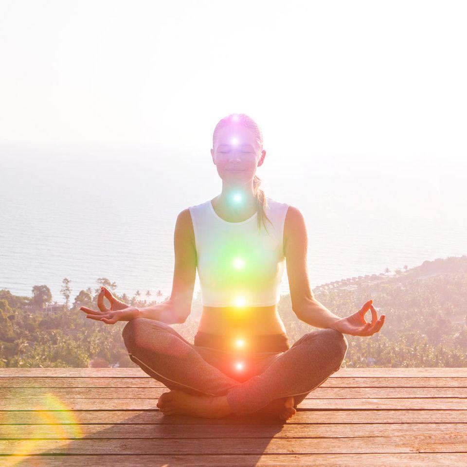 Chakra-Farben: Frau sitzt auf dem Boden und meditiert, dabei leuchten die 7 Chakra-Farben